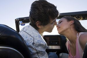Young couple moving in for a kiss in a convertible