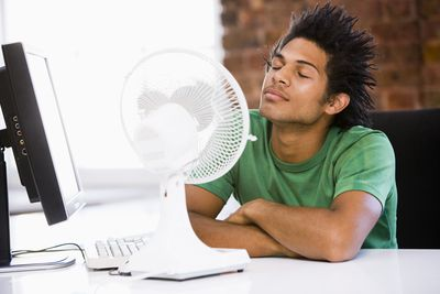 Young man in office with blowing electric fan