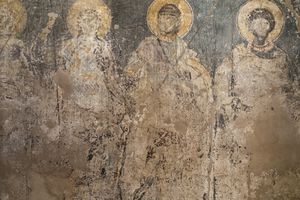ancient artistic rendition of the holy trinity on the old wall