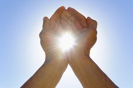 Person cupping hands against sky as to hold sun in between hands