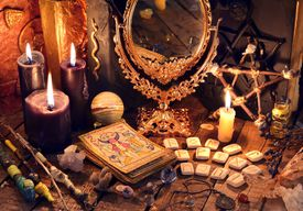 Old books, black candles, mirror, tarot cards and runes