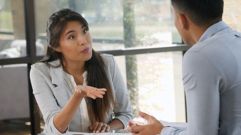 Businesswoman in serious discussion with coworker