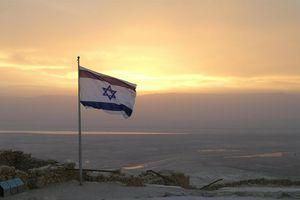 Flag of Israel flying over a sunset landscape.