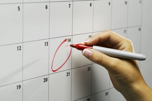 A person circling a date on the calendar.