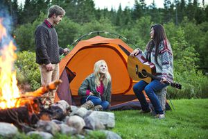 Teens Camping by a Fire and Playing Guitar