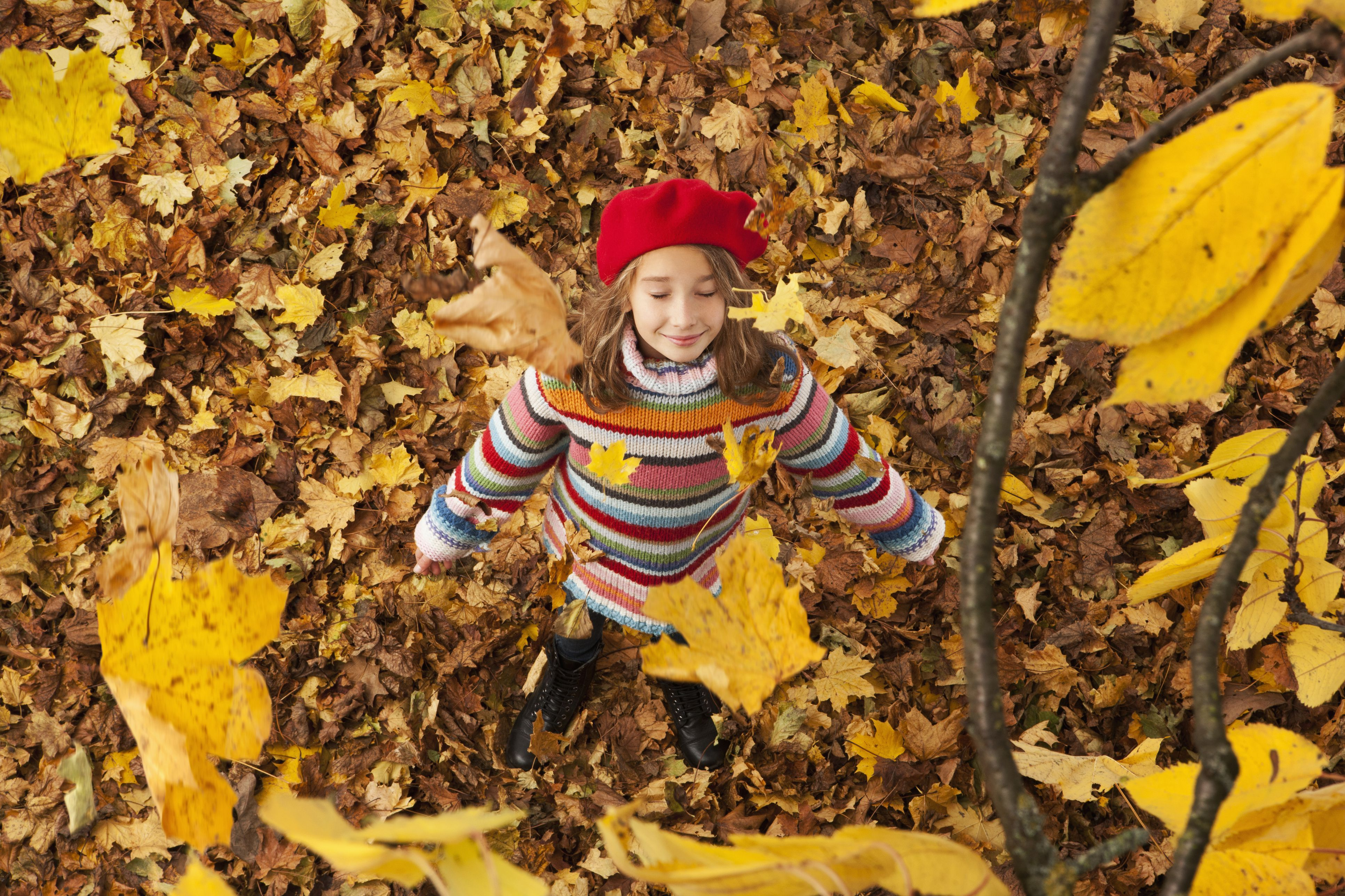 Girl stand in falling autumn foliage