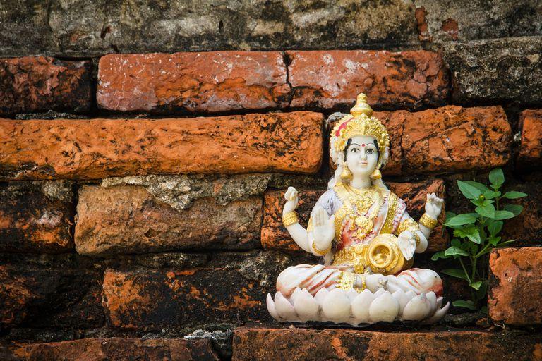 Goddess Lakshmi statue against brick wall