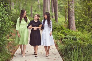 Three young women walking in woods, dressed modestly according to standards of the Pentecostal church