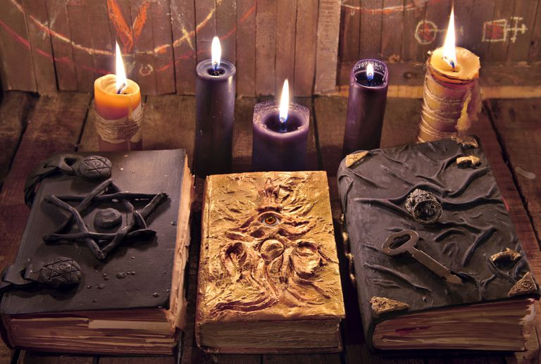 Three magic books with burning candles on planks