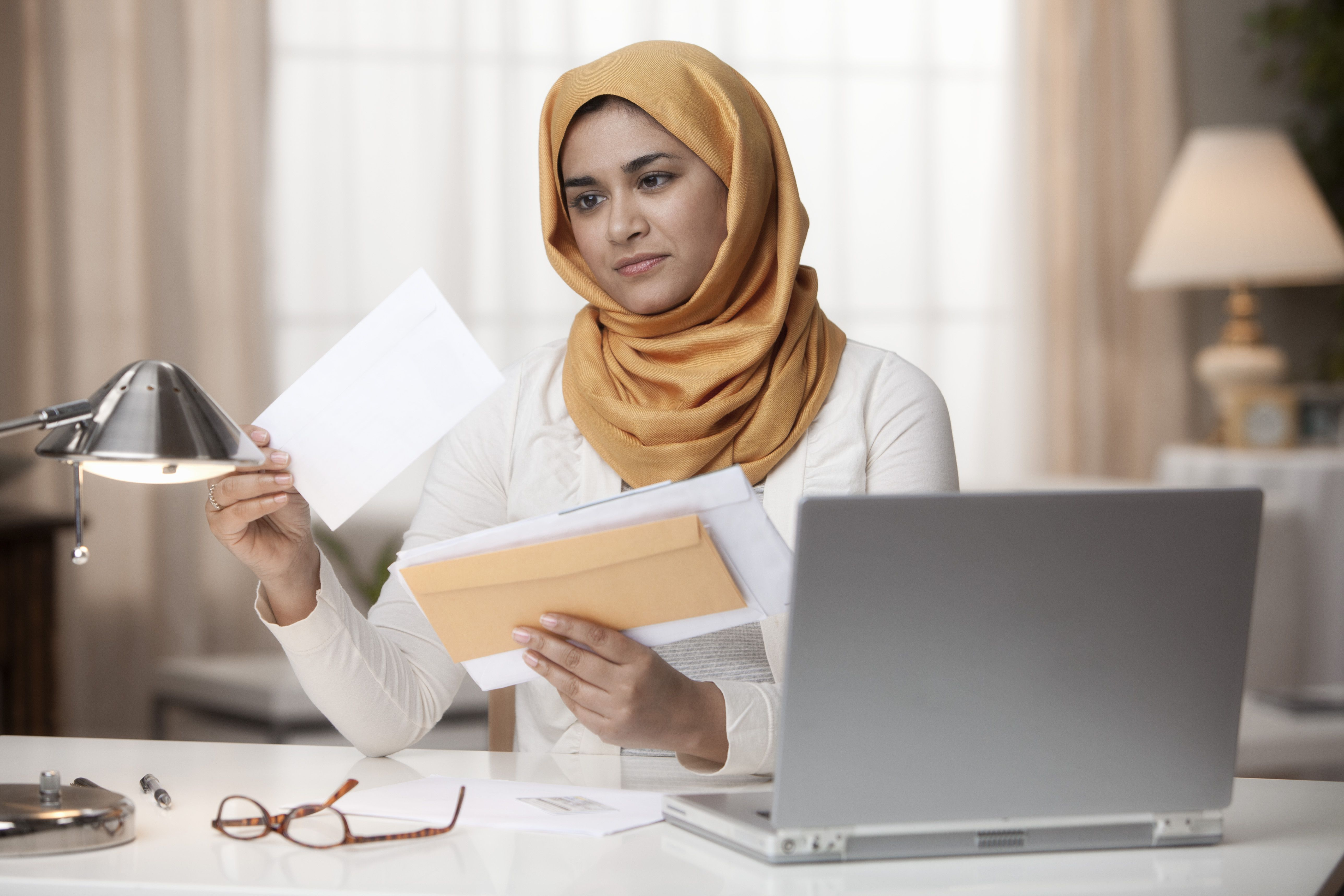 A woman wearing a hijab looks through her mail