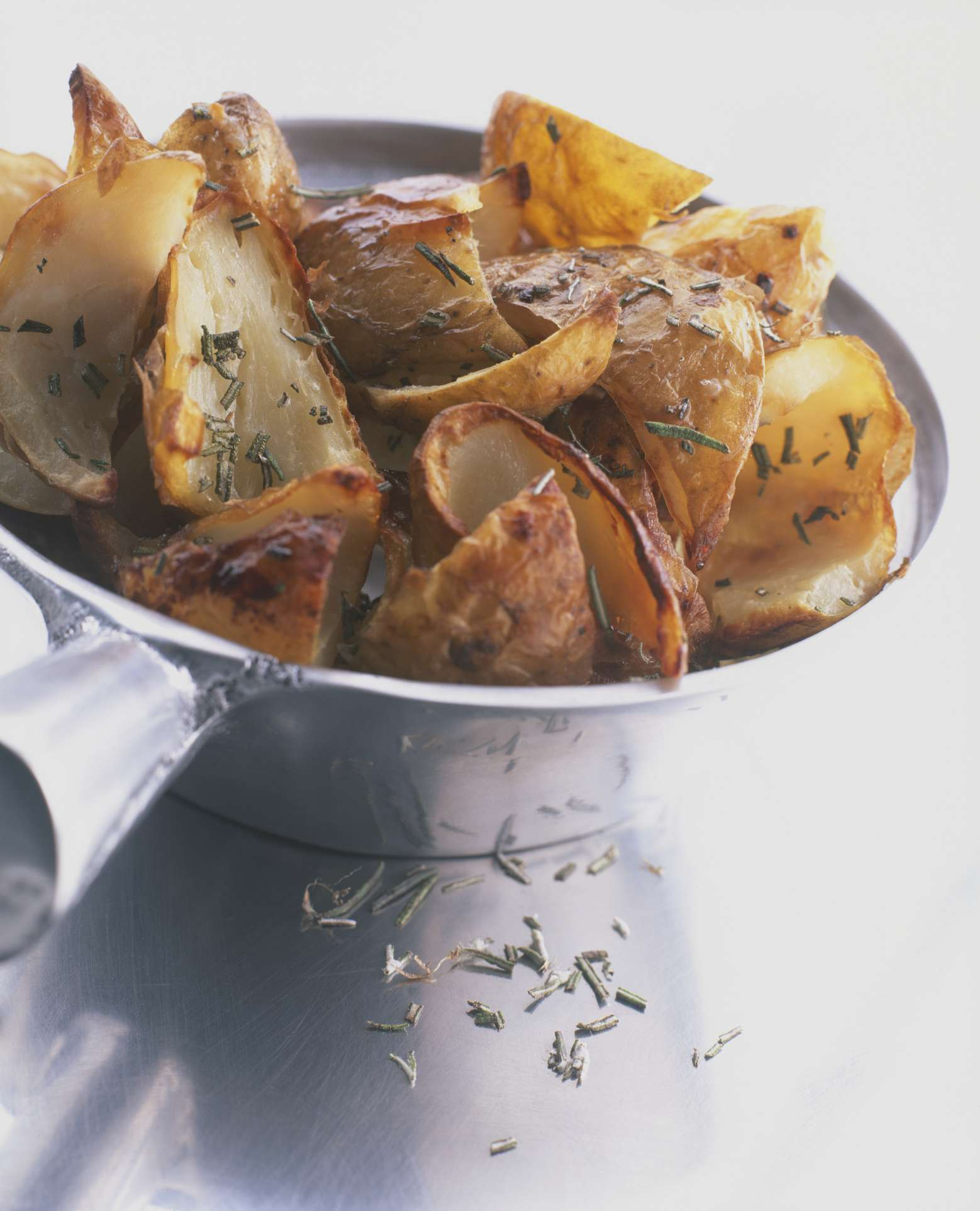 Crispy potato skins sprinkled with rosemary, served in a pan, close-up