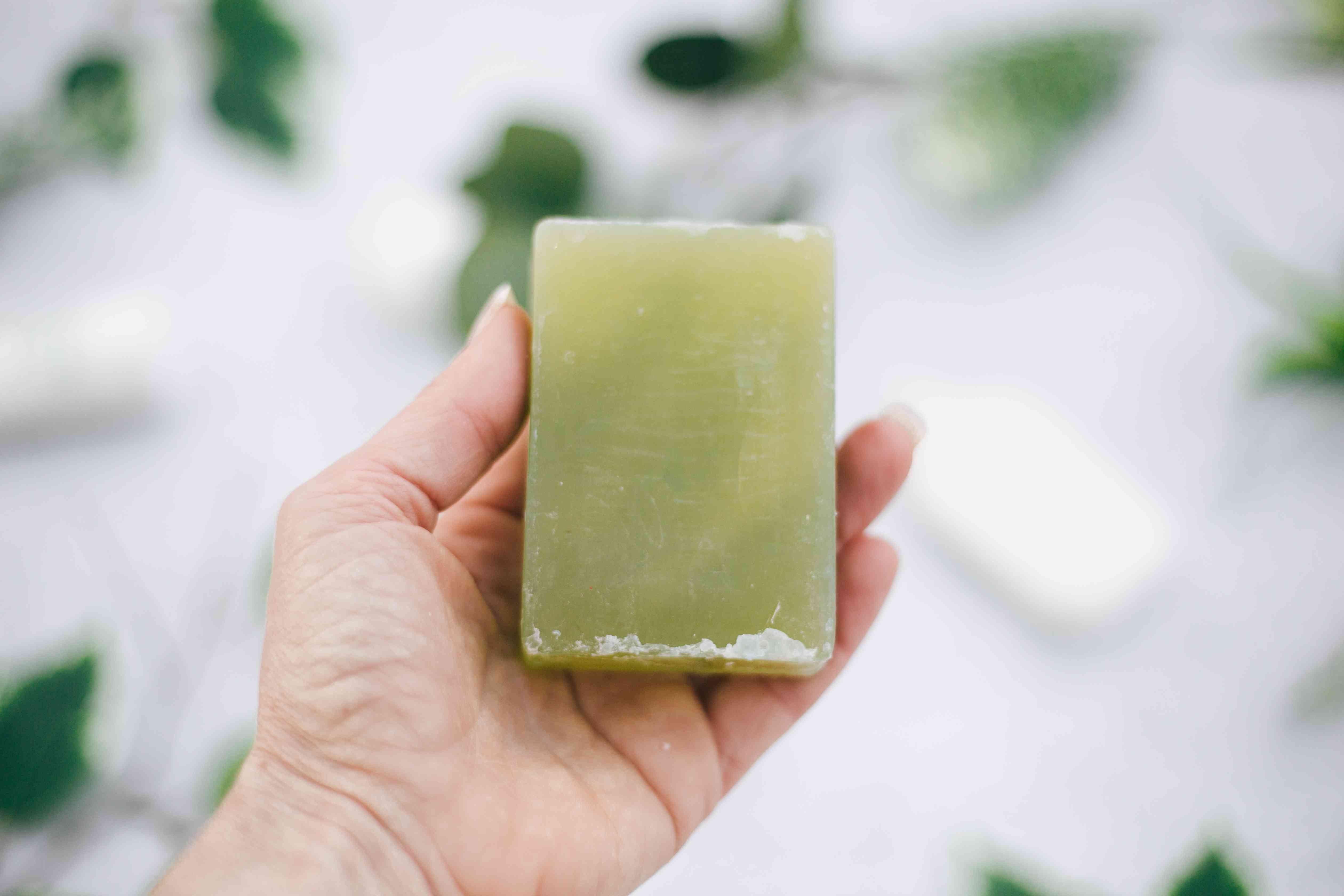 woman hand holding handmade green soap