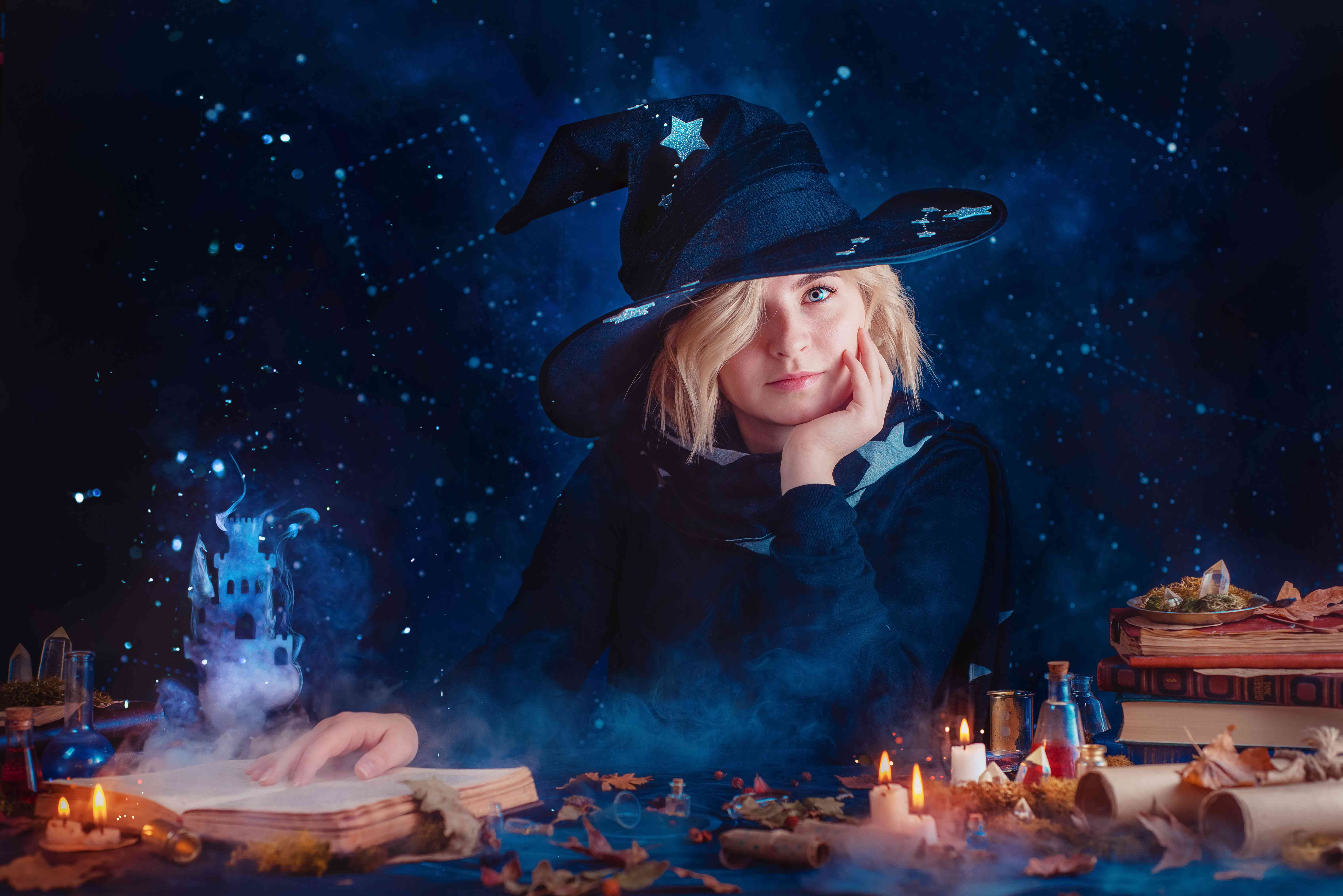 Charming witch in a hat and cloak with stars. Magical workplace with candles, potions and dreamy smoke castle