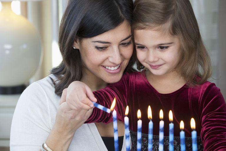 Mother and daughter lighting Hanukah menorah