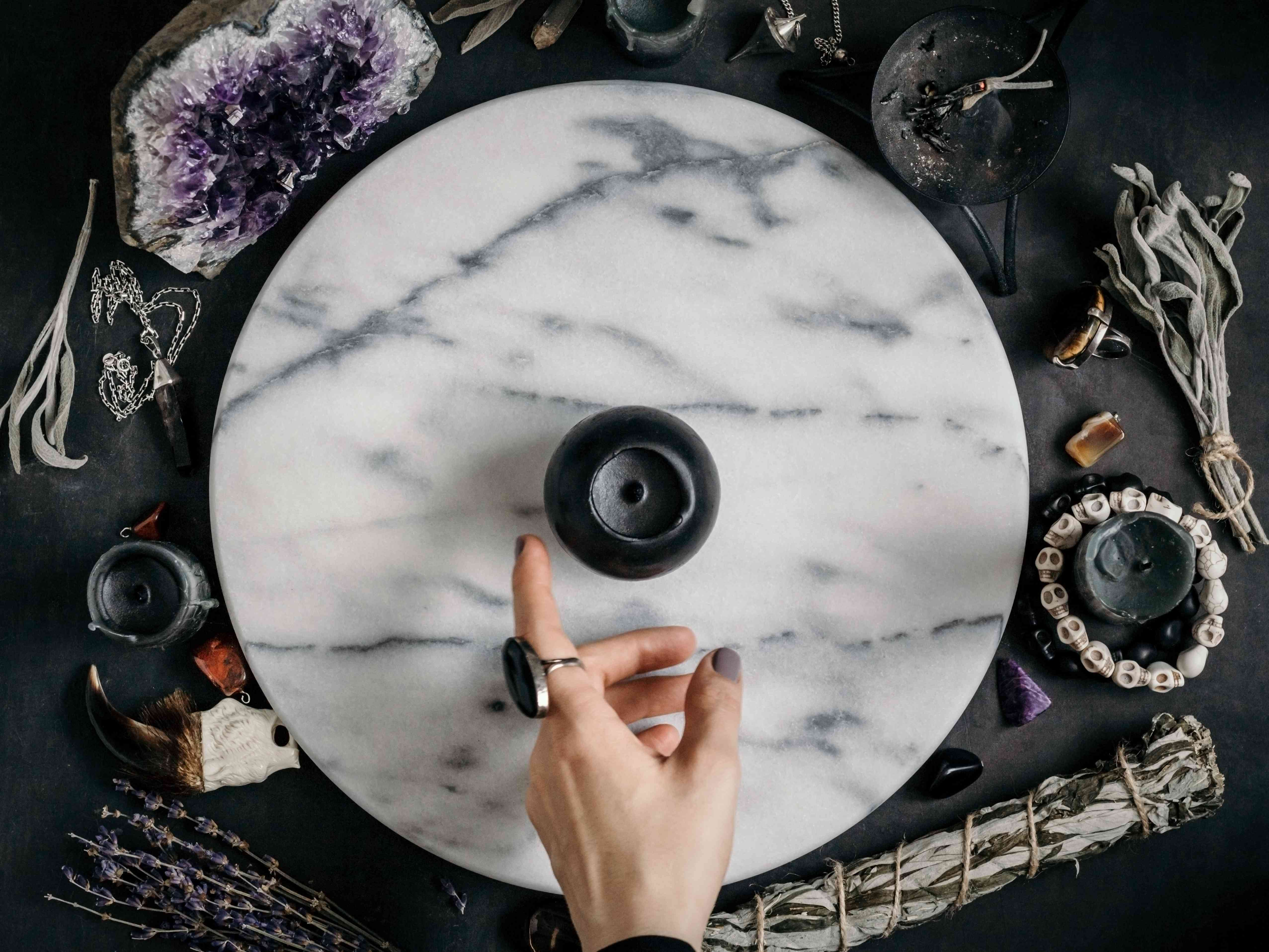 Witch's hand specifies on the black candle on a marble white round tray. The place for witchcraft with magic things around. View from above