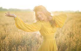 Happy woman in fields with sunlight