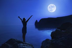 Silhouette of woman on rocky coastline, arms raised in celebration of full moon