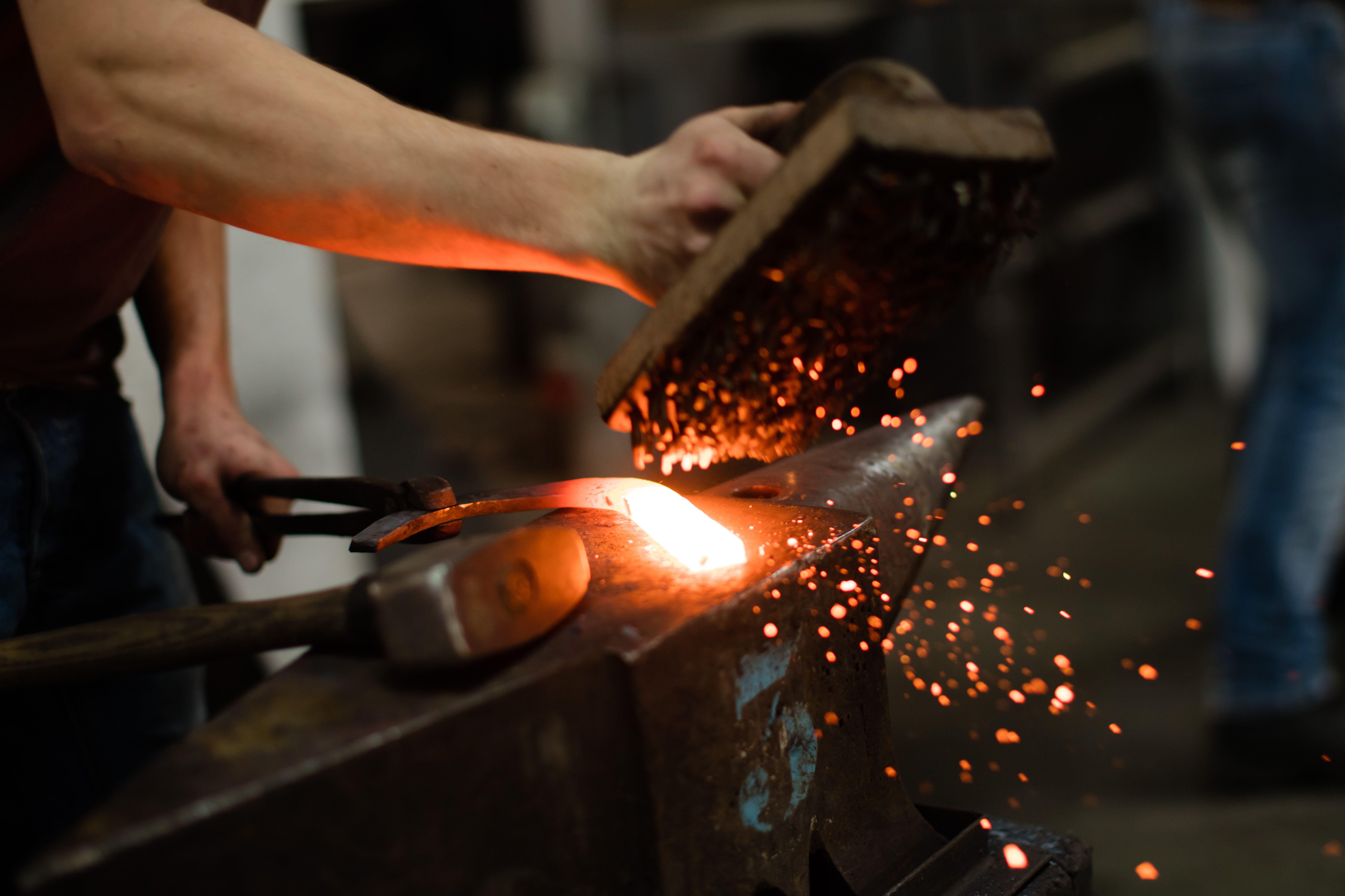 Farrier forging horseshoe on anvil