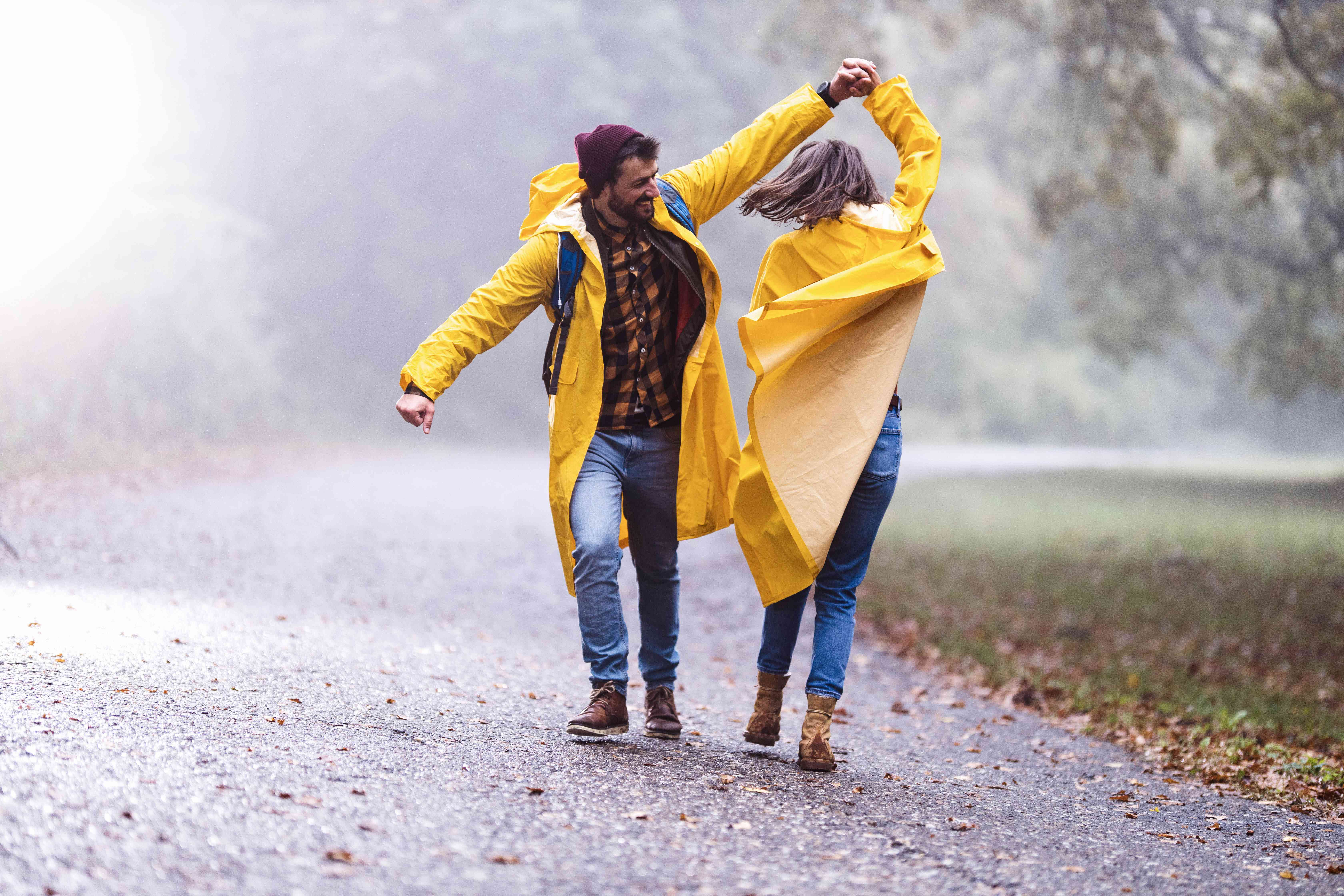 Happy couple in raincoats having fun while dancing on a rain in misty forest.