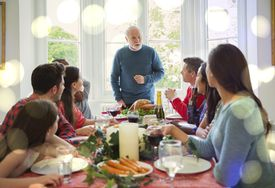 Grandfather speaking at dinner table.