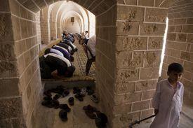 men kneel in mosque