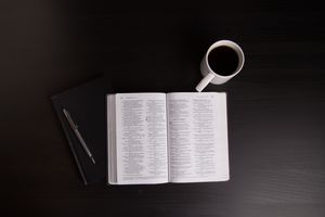 A bible, pen and notebook, and cup of coffee set on table
