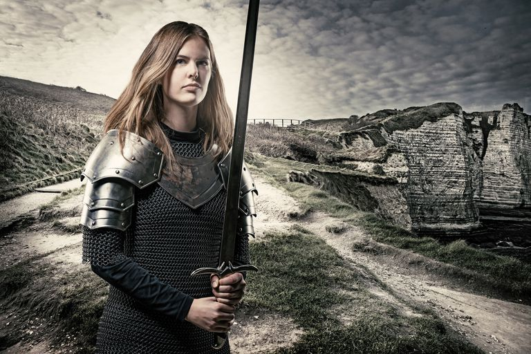 Sword wielding viking warrior young blond female in wild highland countryside