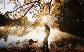 Silhouette of a man and his dog at sunrise.