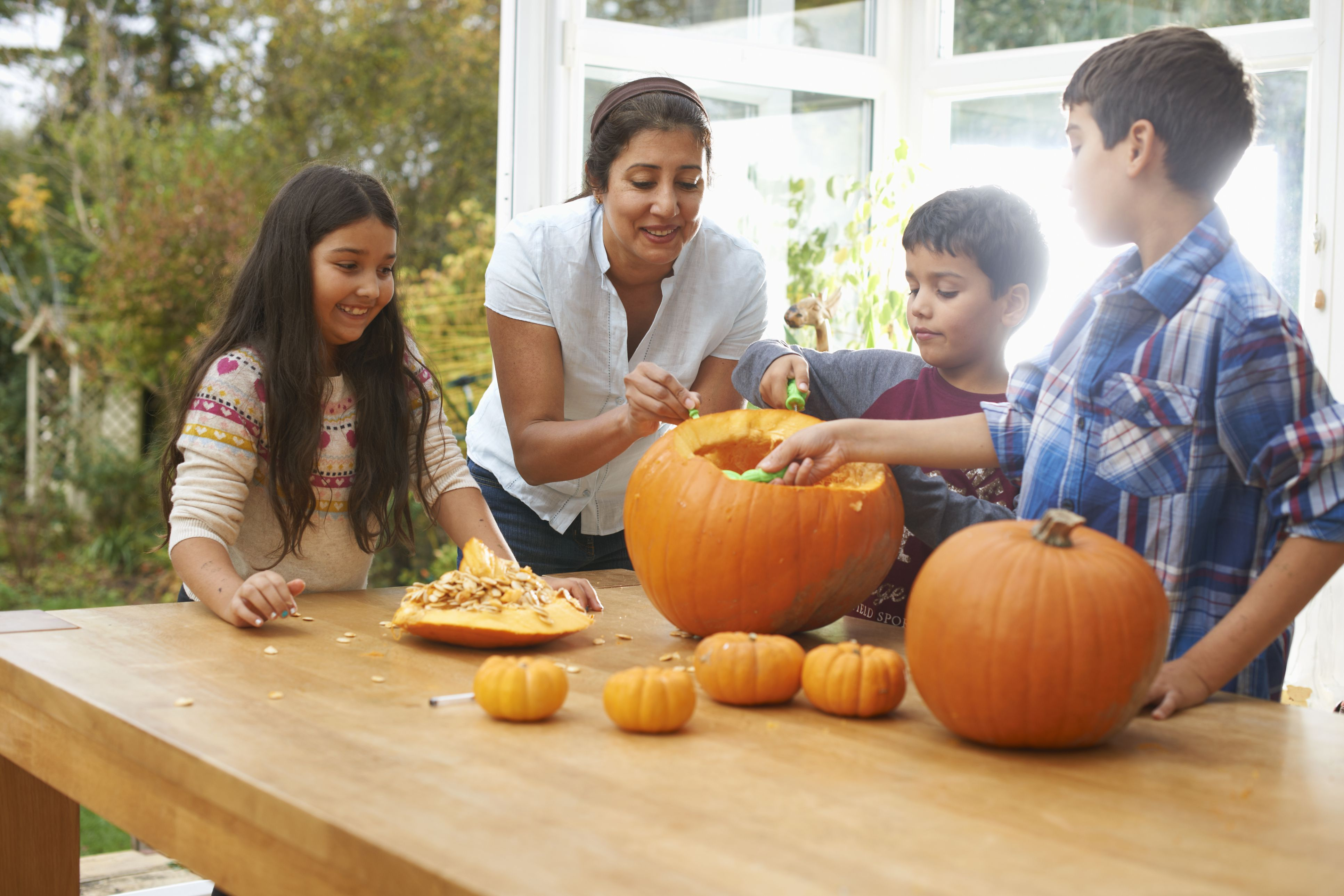Mother and children carving pumpkins