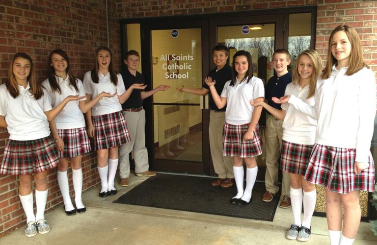 Catholic school children posing at the doors of their school.