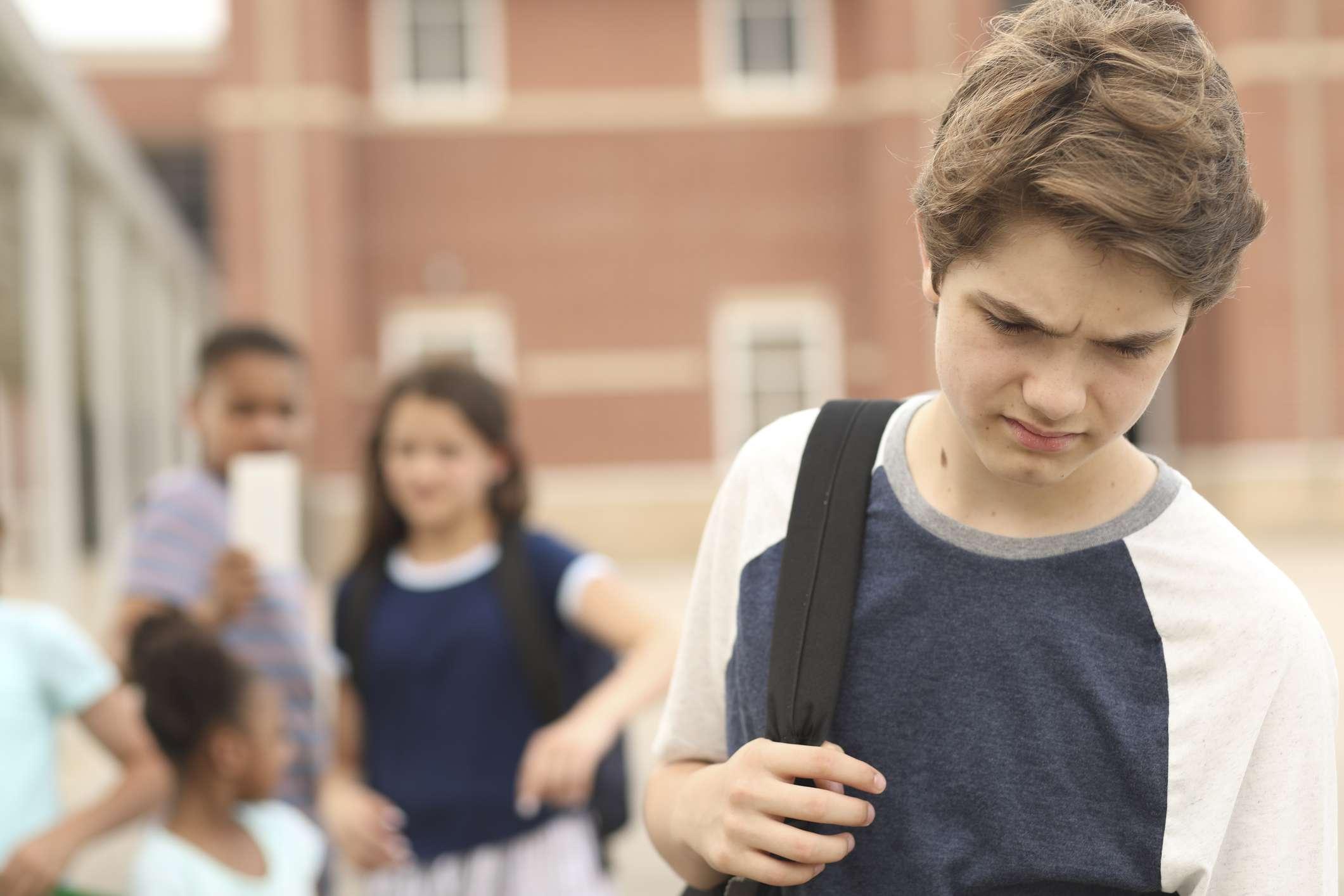 Teen boy walking away from kids