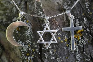 Symbols of Islam, Judaism and Christianity against tree bark