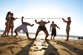 Young adults on beach playing limbo