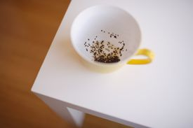 Cup with leftover tea leaves on coffee table, close-up, elevated view