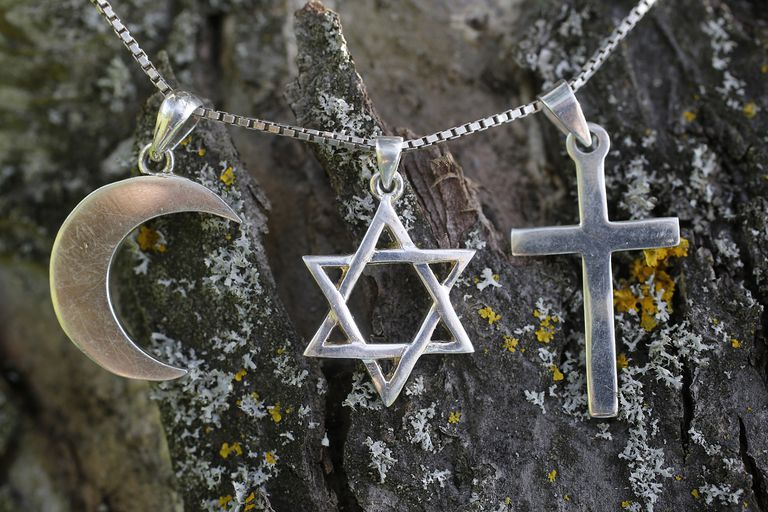 Symbols of Islam, Judaism and Christianity against tree bark