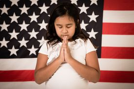 Girl praying in front of American flag