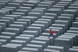 A boy in a red jacket hops from one to another of the 2,711 stellae, concrete tombs that together make a memorial