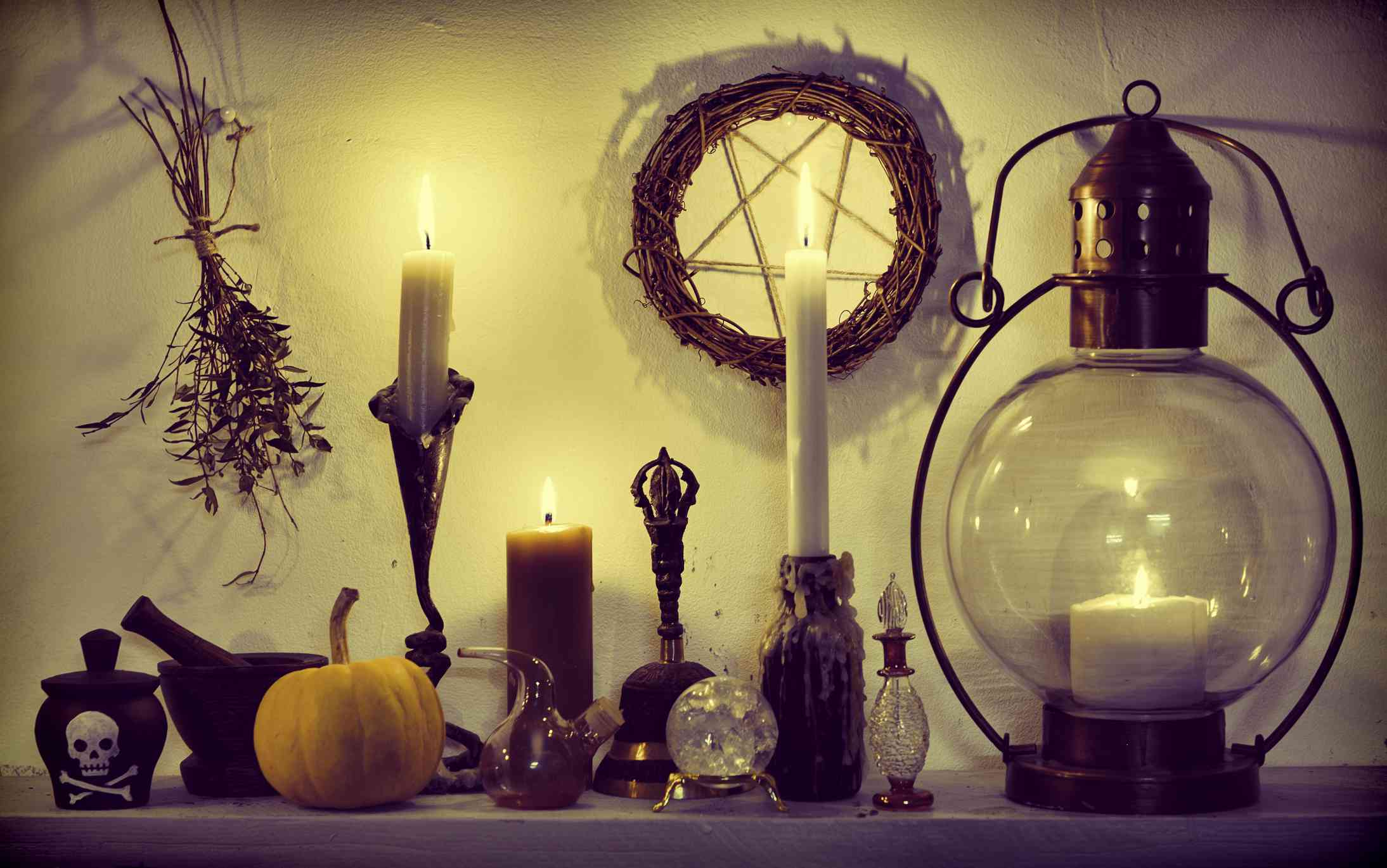 Herbs, pumpkin, crystals, vintage lamp and pentagram on witch table