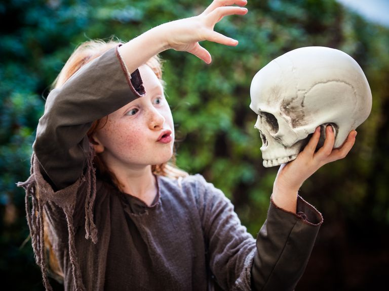 Young girl with skull performing magic spell