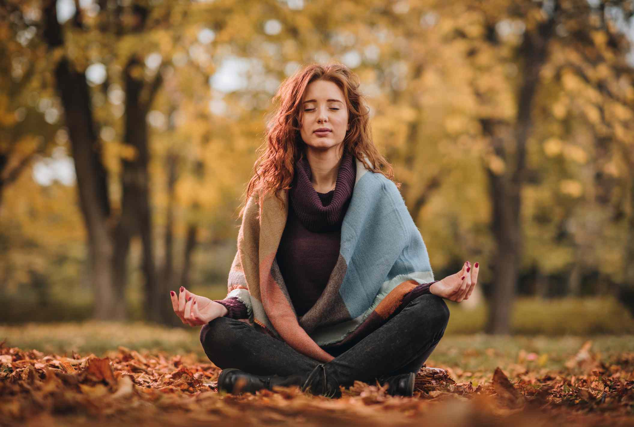 Young woman meditating in Lotus position at the park.