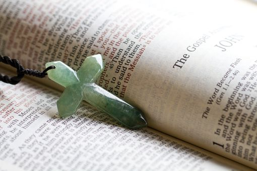 Green crucifix in a Bible open to John 1:1