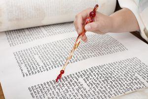A girl uses a Torah pointer