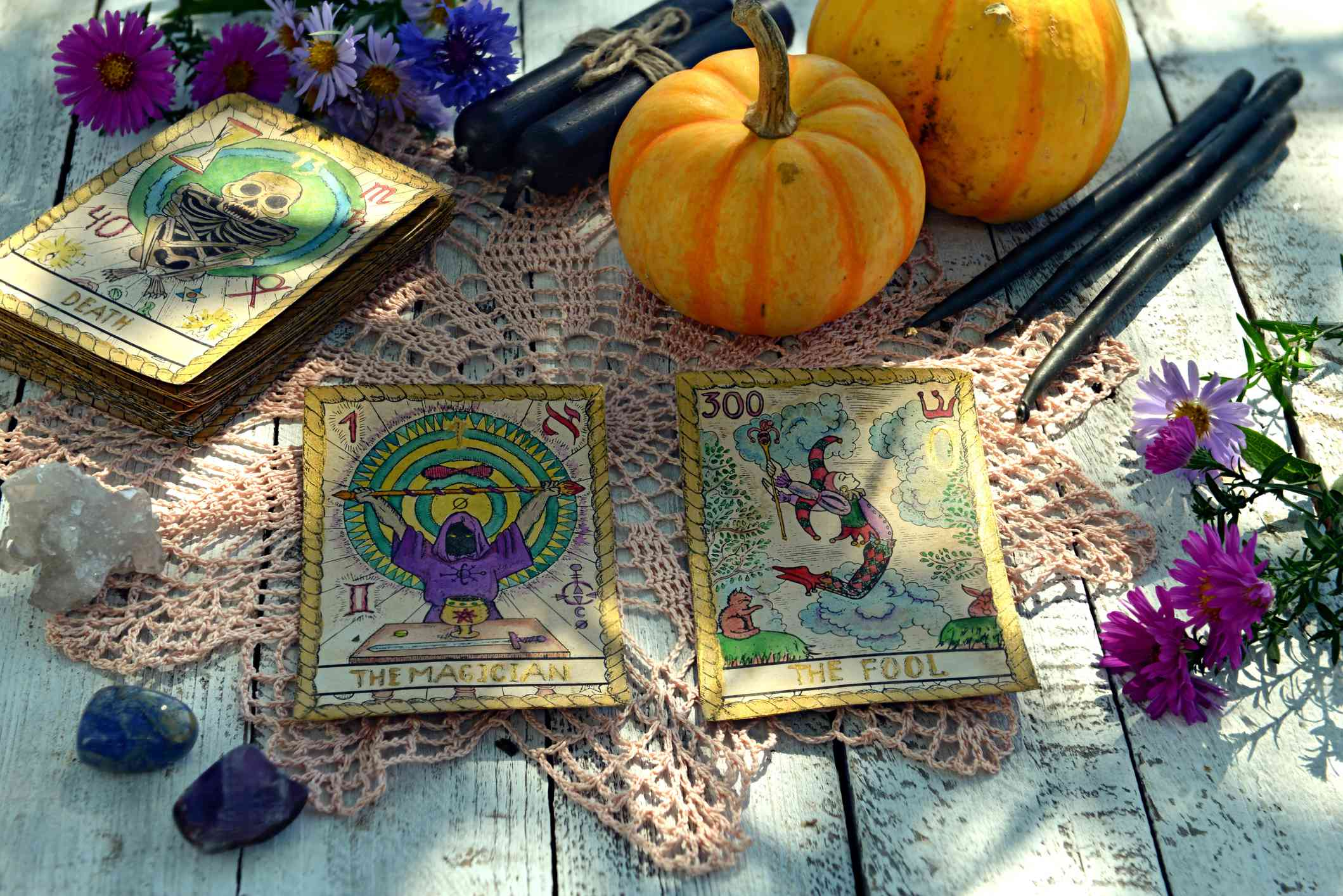 Still life with pumpkins, tarot cards and black candles on old napkin with embroidery