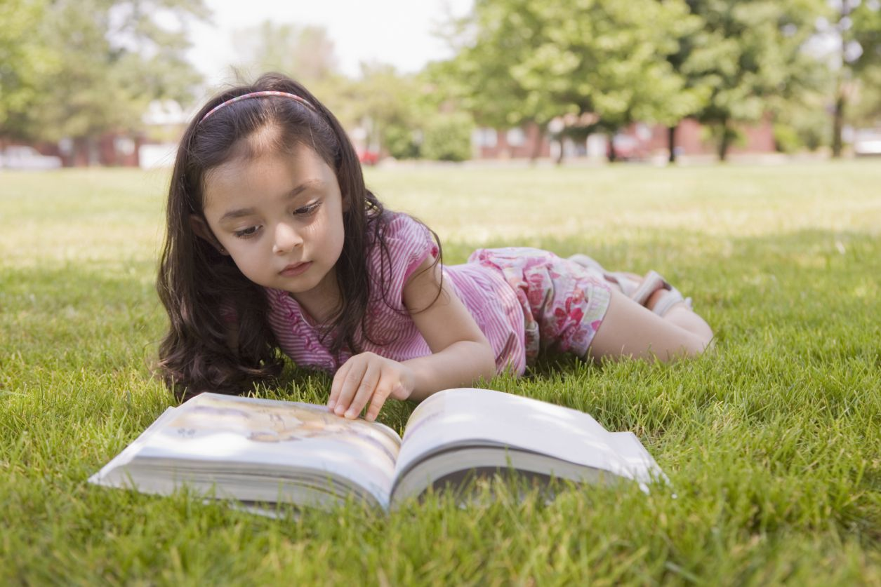 A girl laying in the grass looking at a Bible.