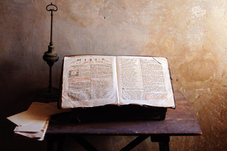 Ancient Bible on Table Against Wall