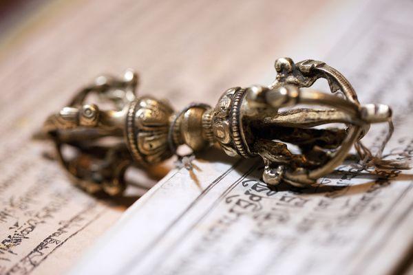 A dorje lies on an open prayer book.