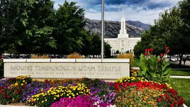 A Mormon temple with colorful flowers in the foreground and mountains in the background.