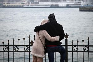 a couple with arms wrapped around each other at waterfront