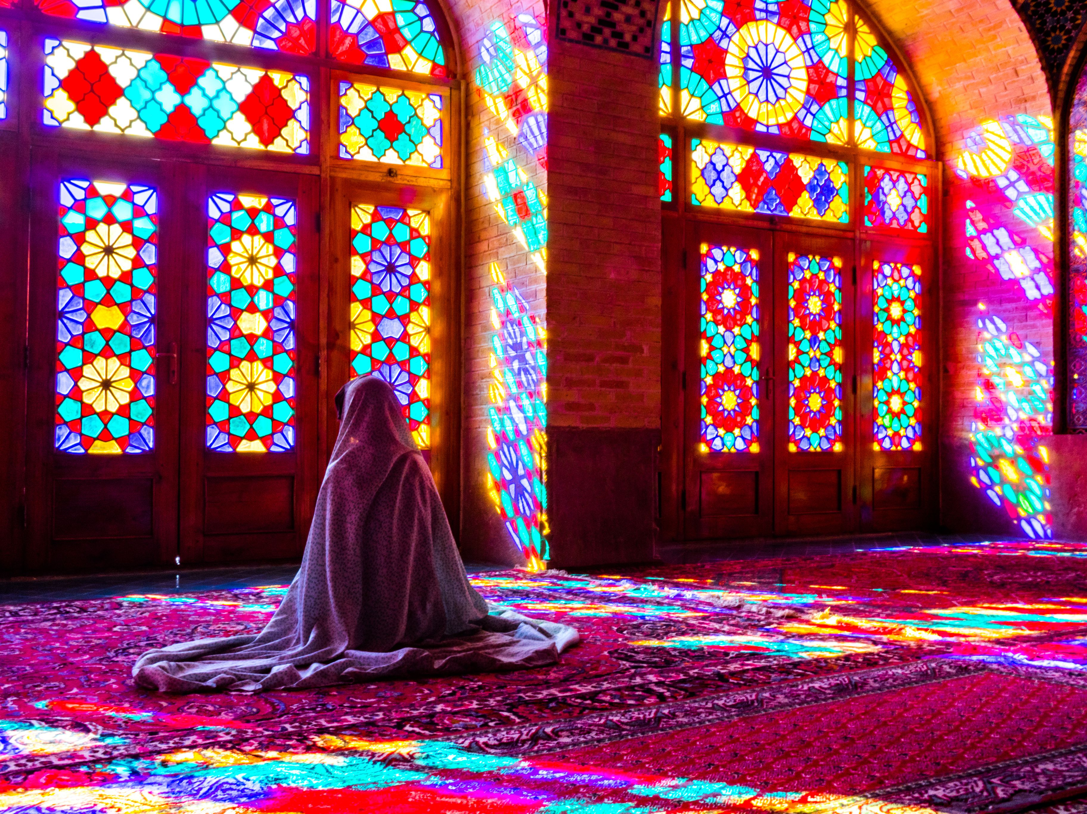 Woman worshipping in front of stained glass windows in Shiraz, Iran