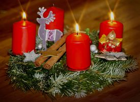 An advent wreath with three red candles lit.